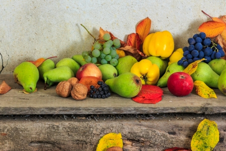 autumnal fruit still life with apples, pears, quince, grapes, nuts, berries and leaves on wooden base photo