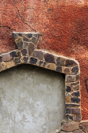 immured doorway with shaped frame of stone on the red cracked plaster texture