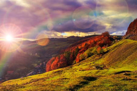 autumn landscape. village on the hillside. forest on the mountain covered with red and yellow leaves. over the mountains the beam of light falls on a clearing at the top of the hill. photo