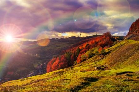 paesaggio autunnale. villaggio sulla collina. bosco sulla montagna coperta di foglie gialle e rosse. oltre le montagne il fascio di luce cade su una radura in cima alla collina. photo