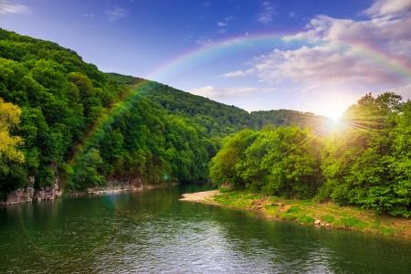 秋の風景です。山のふもとには松林の近くを流れる川の岩の多い海岸。 写真素材