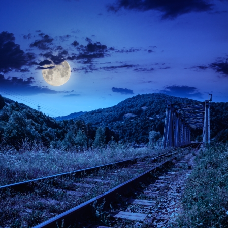 mountains landscape. rail metal bridge in moon light