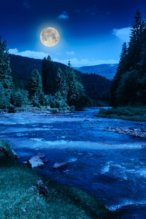 fool moon: river near embankment with trees at the mountain foot with fool moon