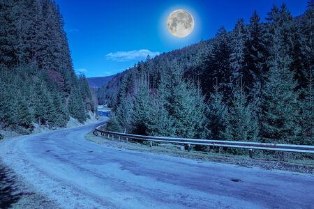 Empty asphalt mountain road near the coniferous forest Stock Photo