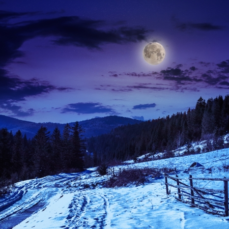 fence by the road to forest in the mountains on a cold winter night