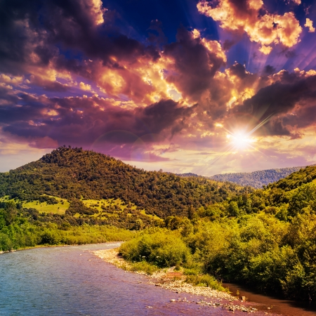 wild river flowing between green mountains on a clear summer evening Stock Photo