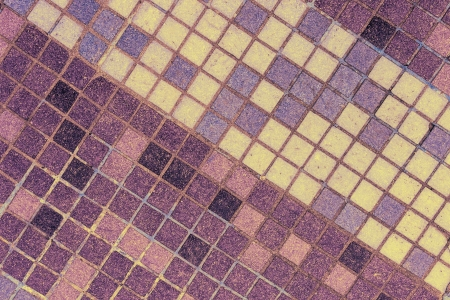 old mosaic tiles of different shades lined with diagonal yellow pattern