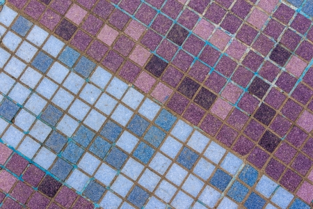 old mosaic tiles of different shades lined with diagonal blue pattern