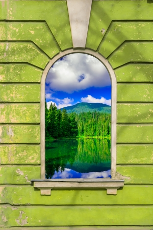 old window frame on the wall with picture of mountain lake