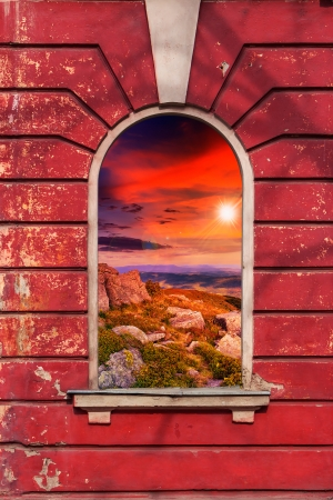 old window frame on the wall with picture of stones on sunset Stock Photo