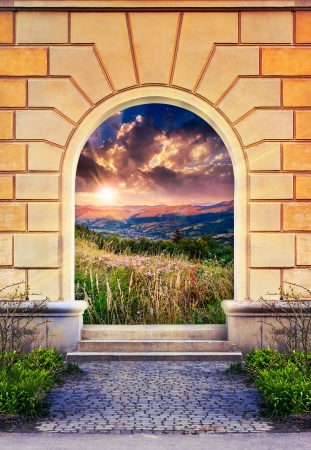 Frame of desolate immured door with picture of mountain meadow on sunrise and steps of cut stone Stock Photo