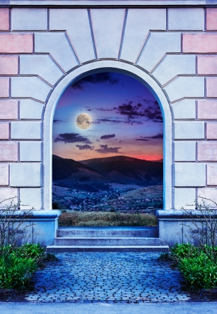 view of a wooden doorway: Frame of desolate immured door with picture of night mountain and steps of cut stone at night Stock Photo