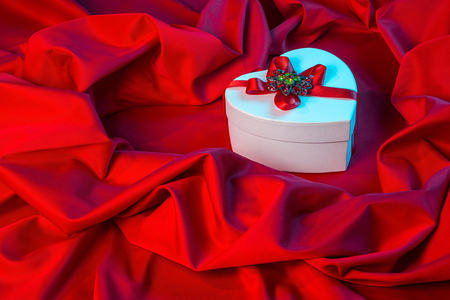 love card. white heart with a red ribbon on a red fabric in blue lighting from right