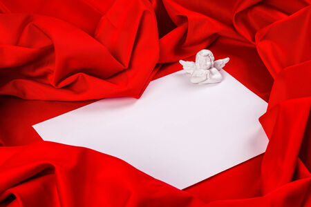 love card. white angel with message card on a red fabric