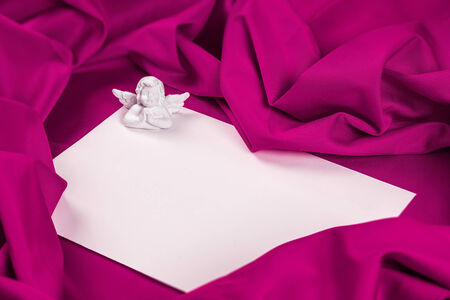 love card. white angel with message card on a purple fabric Stock Photo