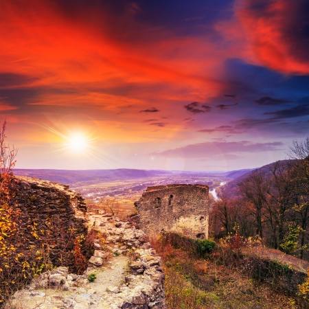 Stone wall of an old ruined castle in the mountains at sunset Stock Photo