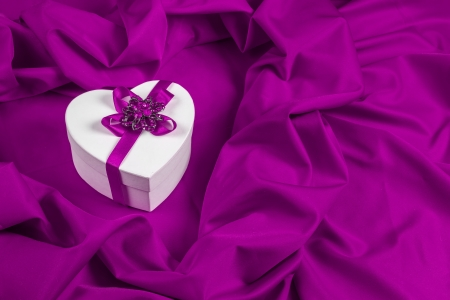 love card. white heart with a purple ribbon on a purple fabric