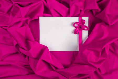 love card. white card with a purple ribbon on a purple fabric photo