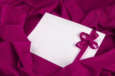 love card. white card with a purple ribbon on a purple fabric