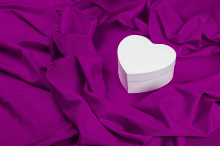 love card. white heart on a purple fabric