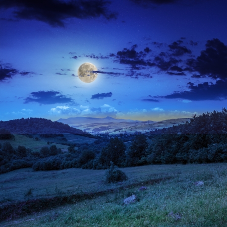autumn landscape. village on the hillside. forest on the mountain. moon light fall on clearing on mountains