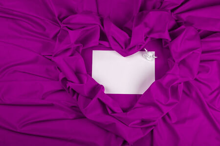 love card. white angel on white card on a purple fabric heart Stock Photo