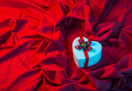 love card. white heart with a red ribbon on a red fabric in blue light Stock Photo