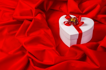 love card. white heart with a red ribbon on a red fabric Stock Photo