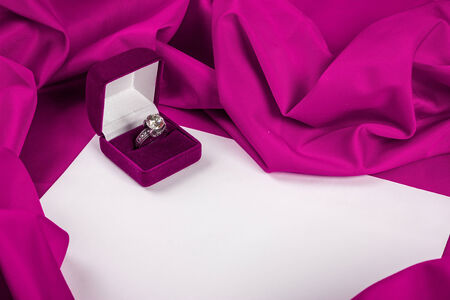 love card. purple jewel box with diamond ring on white paper and purple fabric photo