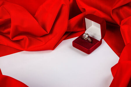 love card. red jewel box with diamond ring on white paper and red fabric