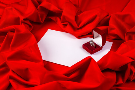 love card. red jewel box with diamond ring on white paper and red fabric photo
