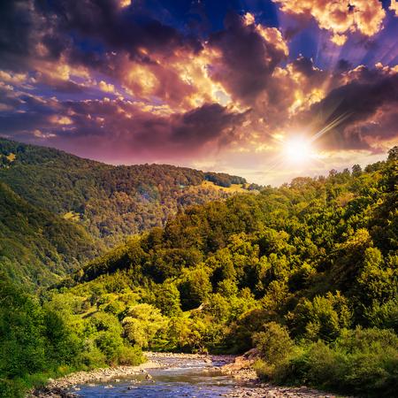 wild river flowing between green mountains on a hott summer sunset