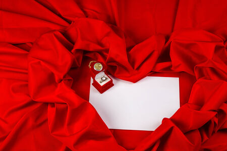 love card. red jewel box with clock and diamond ring on white paper and red fabric