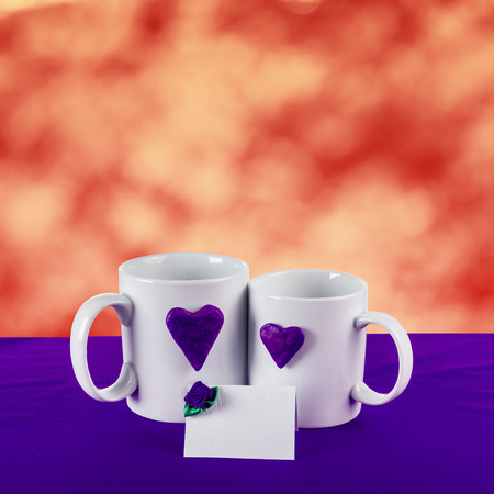 love card with red blur background. blue heart on a white tea cup on a blue fabric