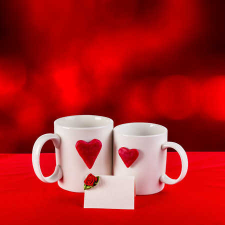 love card with blur background. red heart on a white tea cup on a red fabric