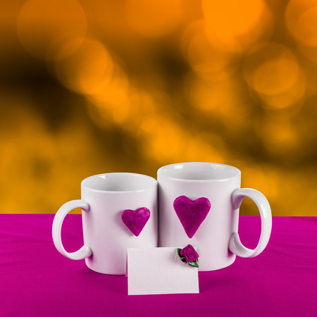 love card with blur background. purple heart on a white tea cup on a gold background photo
