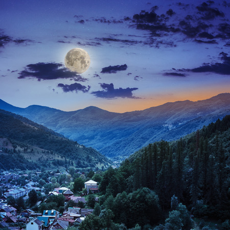 autumn landscape. village on the hillside. forest on the mountain light fall on clearing on mountains at night