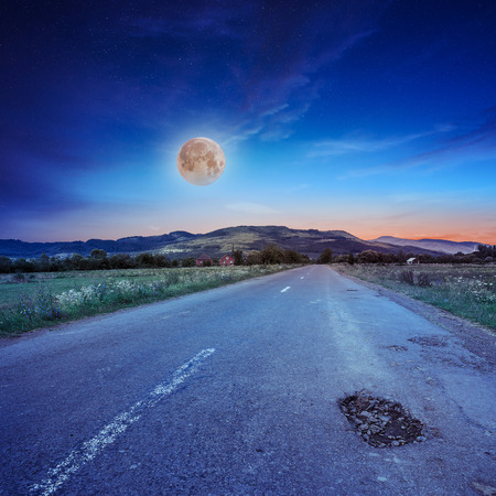 autumn landscape. village by the road with crack. light fall on clearing on mountains in moon light Stock Photo