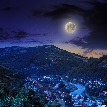 autumn landscape. village by the river. light fall on forest on mountains in moon light Stock Photo