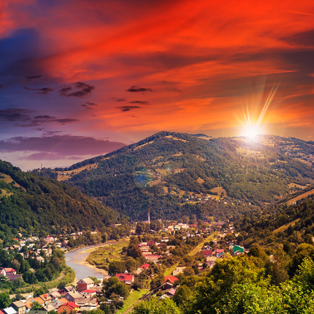 autumn landscape. village by the river. light fall on forest on mountains in evening