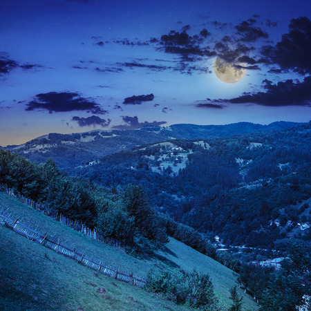 autumn landscape. village on the hillside. forest on the mountain light fall on clearing on mountains in moon light Stock Photo