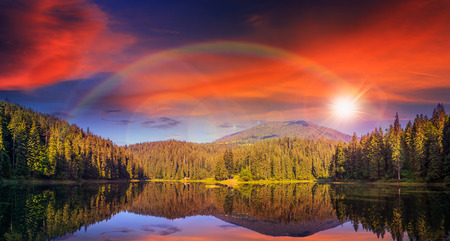 view on lake near the pine forest on mountain background at sunset with rainbow