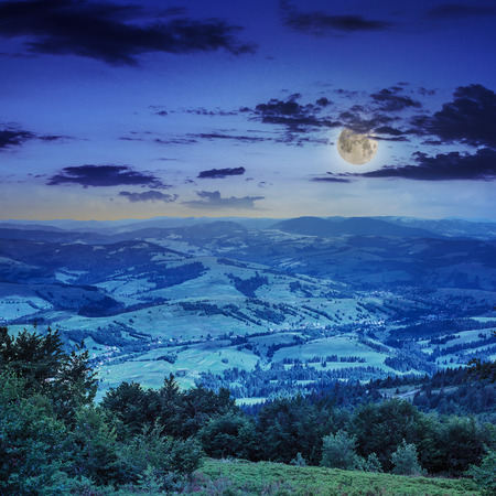 autumn landscape. village on the hillside. forest on the mountain light fall on clearing on mountains at night in moon light