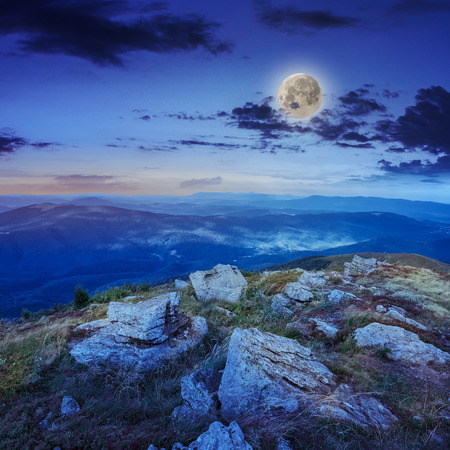 mountain landscape. valley with stones on the hillside.\ forest on the mountain under the moon light on a clearing at the\ top of the hill.