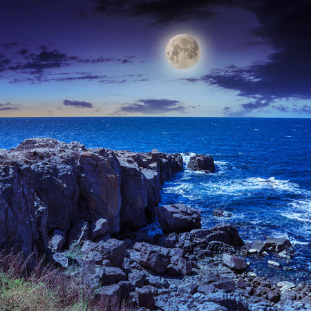 sea ​​wave attacks the boulders and is broken about them at night in evening light Stock Photo