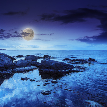 sea wave attacks the boulders and is broken about them at night in moon light