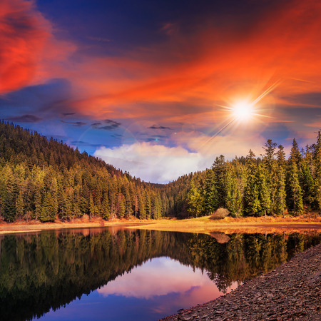 view on lake near the pine forest late in evening on mountain background at sunset Stock Photo