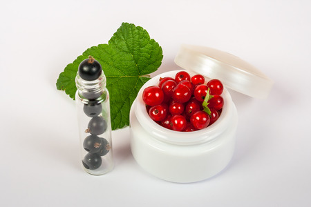 natural cosmetics concept  made of redcurrant and black currant  on white background with green leafs