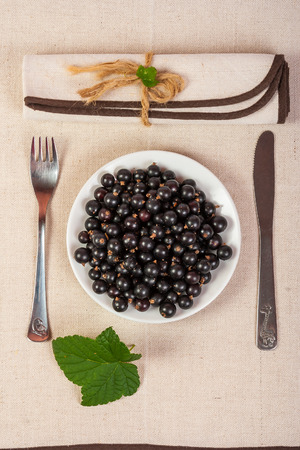 restaurant served black currants in a glass with green leaves