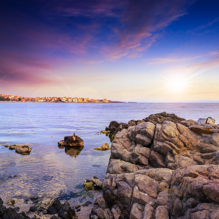 sea coast with boulders near liitle town at sunset Stock Photo